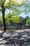 一个小城市广场和一座桥梁的看法在Amstel运河在阿姆斯特丹,荷兰 免版税图库摄影