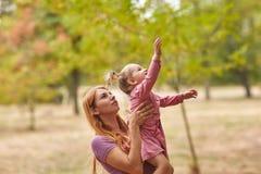 一个小女儿走与妈妈在公园 免版税库存照片