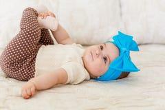 一个小女孩一半每年, 6个月,在逗人喜爱的身体和裙子,有明亮的弓的在头 甜微笑的婴孩 图库摄影