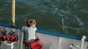 一个小女孩严密地站立与船甲板的板并且看水 股票录像