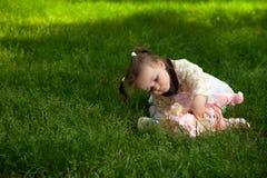 一个小女孩使用与她的玩偶在公园 免版税库存图片