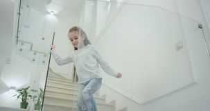 一个小女孩六岁在一个现代房子设计台阶的早晨下来到一楼的她 股票录像