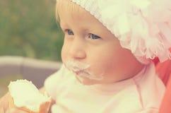 一个小女孩吃着冰淇凌和抹上她的面孔 库存照片