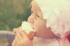 一个小女孩吃着冰淇凌和抹上她的面孔 免版税库存图片