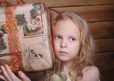 一个小女孩和一个大礼物盒的画象 免版税库存图片