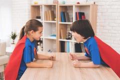 一个小女孩和一个小男孩超级英雄衣服的  他们在一间明亮的屋子测量他们的力量 库存图片