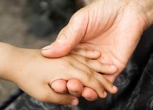 一个小女孩和一个老祖母的手 拿着年长人,世界仁慈天概念的手小孩的 免版税库存照片