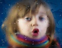 一个小女孩和一个满地露水的窗口的面孔 图库摄影