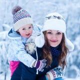 一个小女孩和她的母亲的画象冬天帽子的在雪f 免版税库存图片