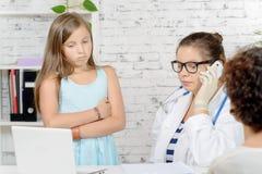 一个小女孩和她的母亲医生的, 免版税库存图片