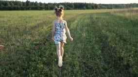 一个小女孩和男孩奔跑横跨领域喜欢飞机 日落往 概念-青年时期,愉快的童年能量  股票录像