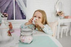 一个小女孩喝茶,拿着杯子 由桌坐 库存图片