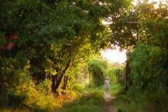 一个小女孩在一个大绿色庭院,一张神仙的不可思议的图片里 免版税库存图片