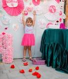 一个小女孩在一条桃红色裙子的一个假日 库存照片