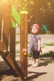 一个小女孩在一架梯子前面在阳光下站立在一个操场 免版税库存照片