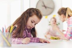 一个小女孩在与色的铅笔的厨房上面画 女孩的母亲有婴孩的准备一个三明治 免版税库存图片