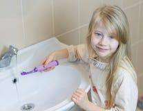 一个小女孩在卫生间洗涤一把电牙刷 免版税库存图片