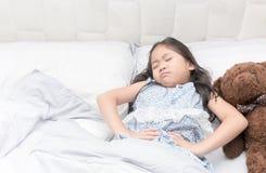 一个小女孩在她的床上有一stomachache 库存照片