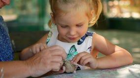 一个小女孩在她的祖母帮助下雕刻黏土小雕象 影视素材