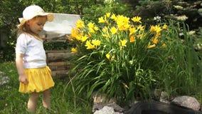 一个小女孩在庭院里吸入花芬芳在一个晴天 股票视频