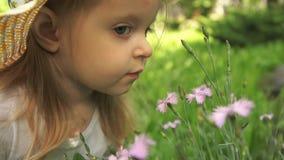 一个小女孩在庭院里吸入花芬芳在一个晴天 股票录像