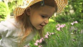 一个小女孩在庭院里吸入花芬芳在一个晴天 影视素材