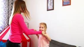 一个小女孩在握她的在慢动作的沙发跳姐妹` s手 股票录像