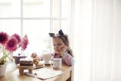 一个小女孩在桌上由窗口吃着早餐 古色古香的企业咖啡合同杯子塑造了新鲜的早晨好老笔场面打字机 复制空间 免版税图库摄影