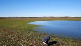 一个小女孩在湖附近在春天走 股票视频