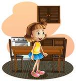 一个小女孩在穿着一条蓝色裙子的厨房里 图库摄影