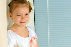 一个小女孩坐在背景的窗口  图库摄影