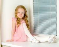 一个小女孩坐在背景的窗口  库存图片