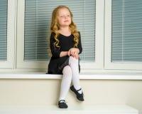 一个小女孩坐在背景的窗口  免版税库存图片