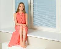 一个小女孩坐在背景的窗口  库存照片