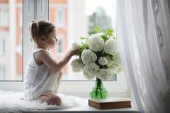 一个小女孩坐窗台 花束开花例证向量 免版税库存图片