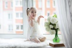 一个小女孩坐窗台 花束开花例证向量 库存照片