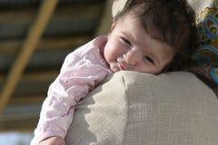 一个小女孩婴孩的画象的关闭她的母亲的拥抱 免版税库存照片
