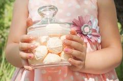 一个小女孩拿着一个瓶子蛋白软糖 免版税库存图片