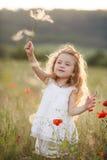 一个小女孩用在夏天草甸的一个蒲公英 免版税库存照片