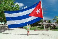 一个小女孩的出色的意见舒展她的胳膊的热带海滩的对古巴旗子 库存图片