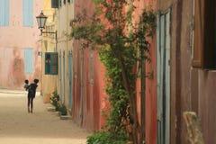 一个小女孩的剪影一条色的街道的在Gorée海岛在塞内加尔 免版税图库摄影