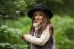 一个小女孩的春天画象 有大棕色眼睛的甜女孩在黑帽会议和毛皮授予 免版税库存照片