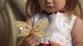 一个小女孩的特写镜头一只金黄蝴蝶的 影视素材