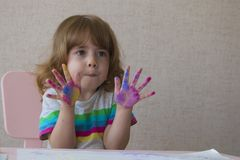 一个小女孩的画象有被绘的棕榈的 女孩坐椅子在桌上 免版税图库摄影