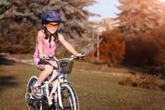 一个小女孩的画象盔甲的在一辆自行车在夏天公园 库存图片