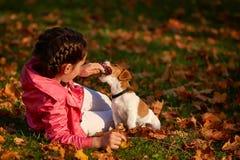 一个小女孩的画象被弄脏的桔子背景的在一个秋季晴天离开 免版税库存图片