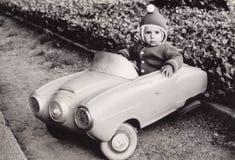 一个小女孩的老摄影玩具汽车的 免版税库存照片