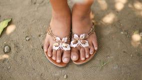 一个小女孩的被晒黑的腿板岩的与一只装饰蝴蝶 赤足女孩在沙子的夏天鞋子 菲律宾 库存照片