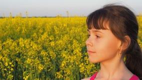 一个小女孩的面孔本质上 孩子的面孔是特写镜头 孩子是在黄色花 油菜籽领域 股票视频