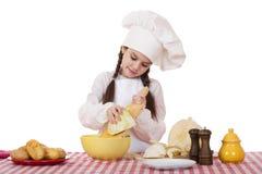 一个小女孩的画象一块白色围裙和厨师帽子细片的c 库存照片